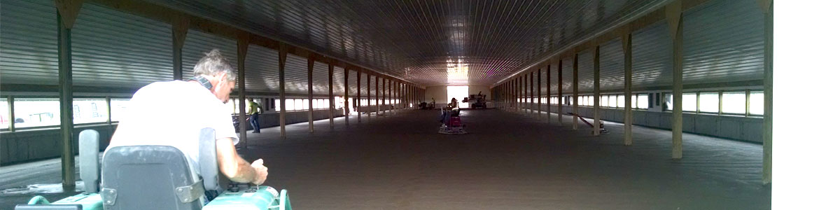 Van Haren Constructions' crew polishing and smoothing the concrete floor of a large agricultural barn