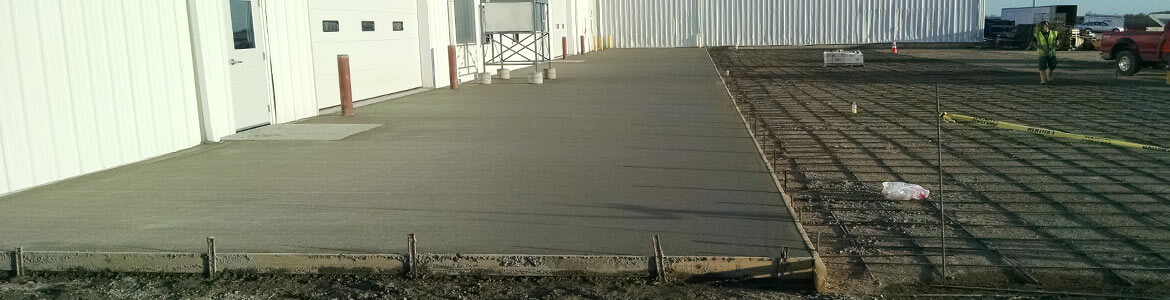 Freshly poured concrete slab outside a commercial building